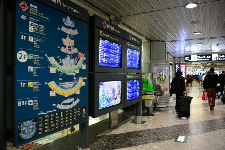 北海道新千歳空港内でスーツケースを持ち行き交う人々の様子